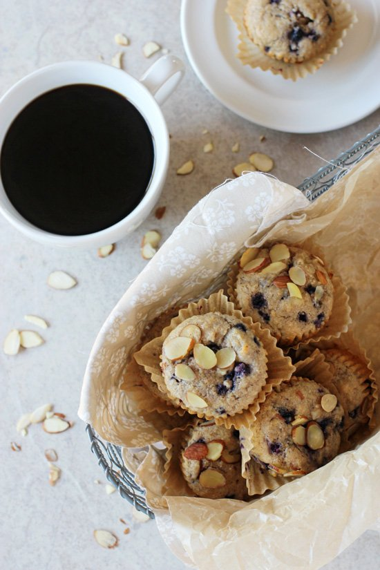 Recipe for blueberry almond whole grain muffins. With whole wheat flour, oat bran and sweetened with honey and maple syrup. Packed with blueberries!