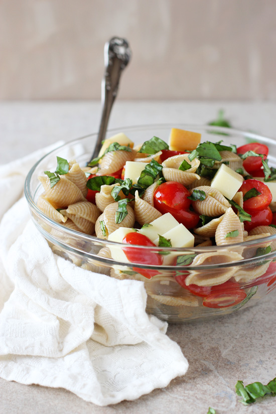 Recipe for a quick and easy caprese pasta salad. With a twist! With smoked mozzarella, loads of fresh basil, cherry tomatoes and a simple balsamic dressing!