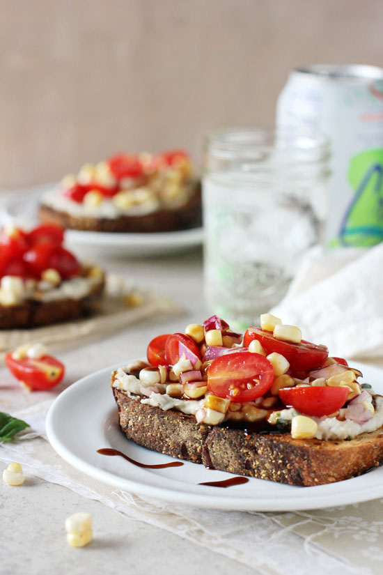Recipe for quick and easy fresh corn and tomato open-faced sandwich. With a basil-packed white bean spread, a corn and tomato topping and balsamic glaze!