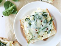 These easy spinach artichoke french bread pizzas are a perfect weeknight recipe! A fun and lighter spin on classic spinach artichoke dip!