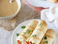Filled with colorful veggies, cashews and fresh ginger, these baked thai vegetable taquitos are a family favorite! Served with an orange peanut sauce for dipping!