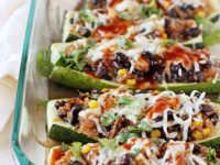 Simple & fun BBQ quinoa stuffed zucchini! Tender zucchini filled with quinoa, black beans, veggies and flavorful BBQ sauce. Topped with a touch of cheese!