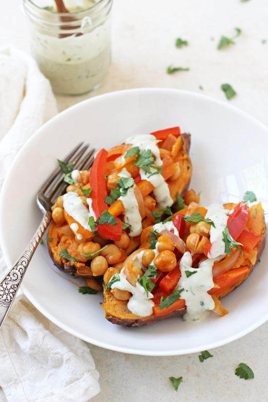 Hearty & healthy buffalo chickpea stuffed sweet potatoes! With a spicy chickpea and veggie filling, and a creamy, cooling ranch drizzle!