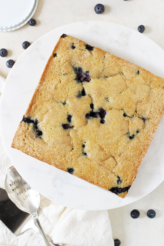 A Blueberry Buttermilk Cake on a marble cake stand.