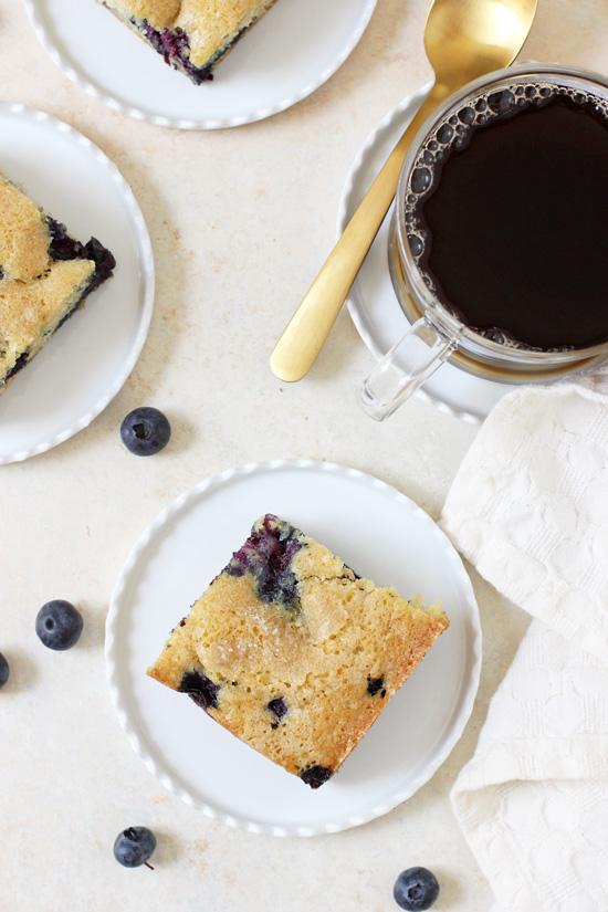 Three pieces of Lemon Blueberry Buttermilk Cake on small white plates.
