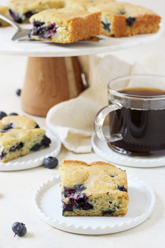 Two slices of Blueberry Buttermilk Breakfast Cake with a cup of coffee.