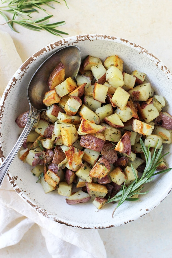 A white bowl filled with Roasted Red Potatoes and a serving spoon.
