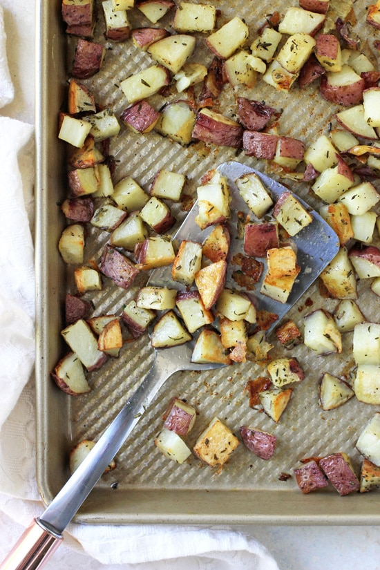 A rimmed baking sheet filled with red potatoes and a spatula.