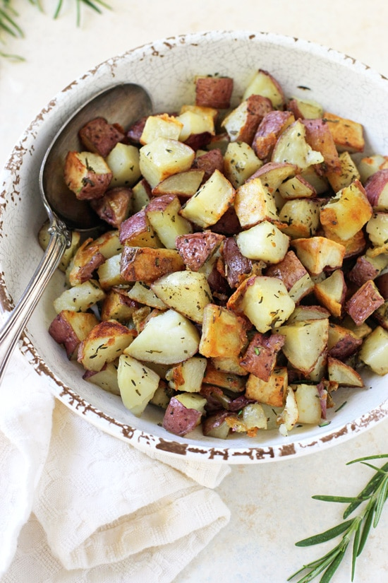 A white bowl filled with Oven Roasted Red Potatoes.