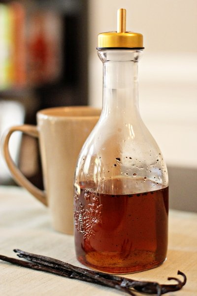A glass jar of Homemade Vanilla Syrup with a mug in the background.