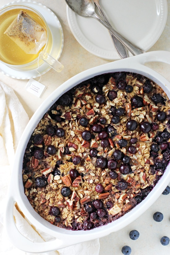 A baking dish of Baked Blueberry Apple Oatmeal with tea to the side.