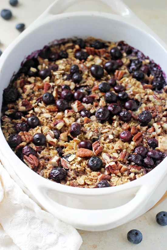 A white casserole dish filled with Baked Blueberry Apple Oatmeal.