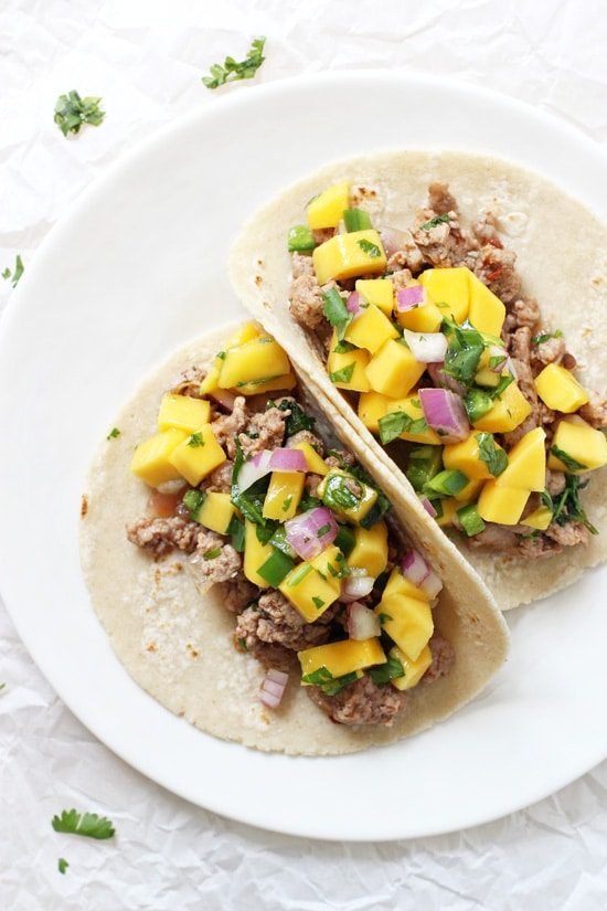 Two Pork Tacos with Mango Salsa on a white plate.