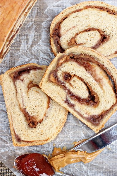 Three slices of Peanut Butter and Jelly Swirl Bread on wax paper.
