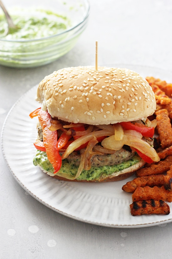 A Pesto Turkey Burger on a white plate with sweet potato fries.