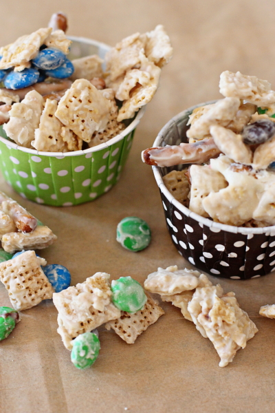 Two colorful baking cups filled with White Chocolate Snack Mix.