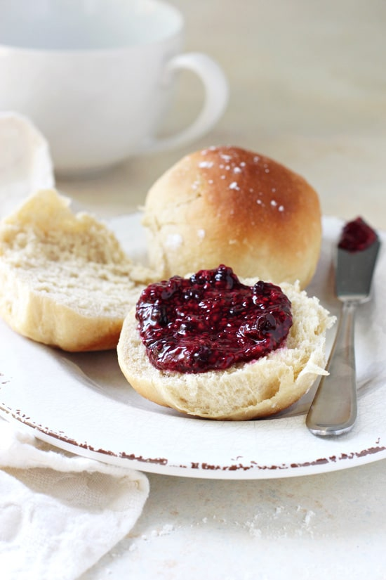 A Honey Dinner Roll split open on a plate and slathered with jam.