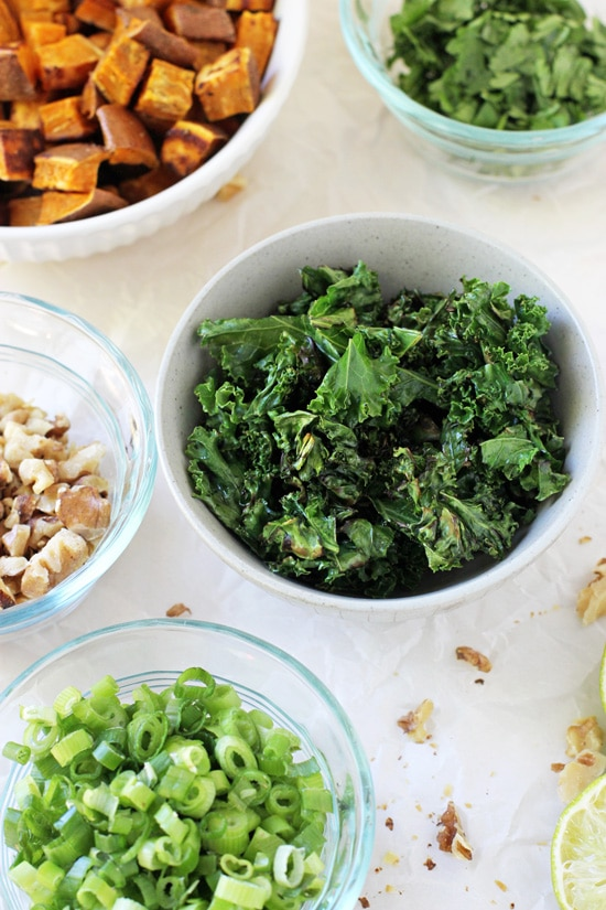 Small bowls filled with kale, green onion, walnuts and sweet potatoes.