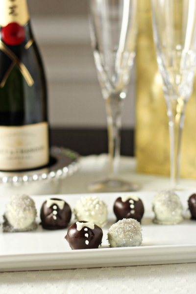 Bride and Groom Truffles on a white platter with champagne in the background.