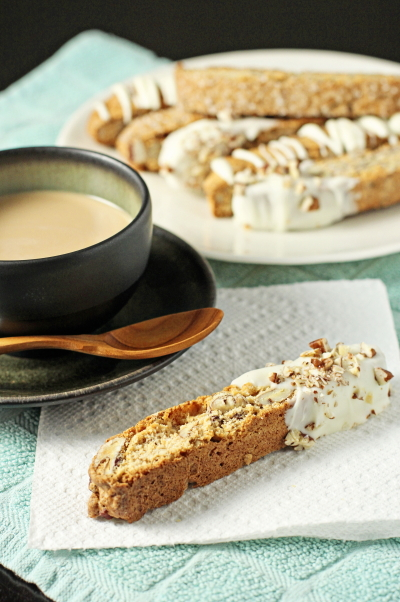 Pecan Biscotti on a plate and napkin with a cup of coffee.