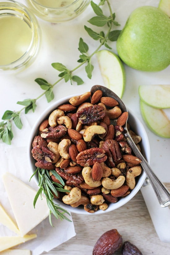 A white bowl filled with Spiced Rosemary Thyme Nuts with a spoon in the dish.