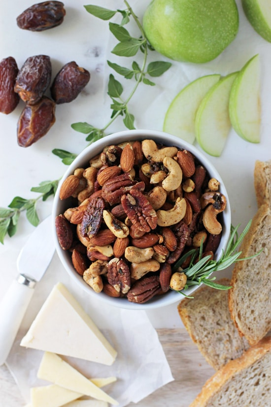 Spiced Rosemary Nuts on a marble platter with bread, fruit and dates.