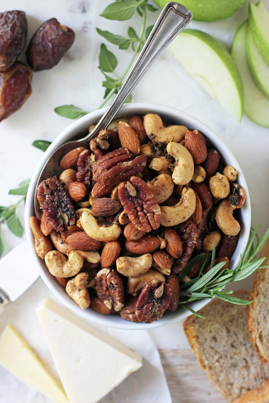 A bowl filled with Spiced Holiday Nuts on a marble appetizer platter.