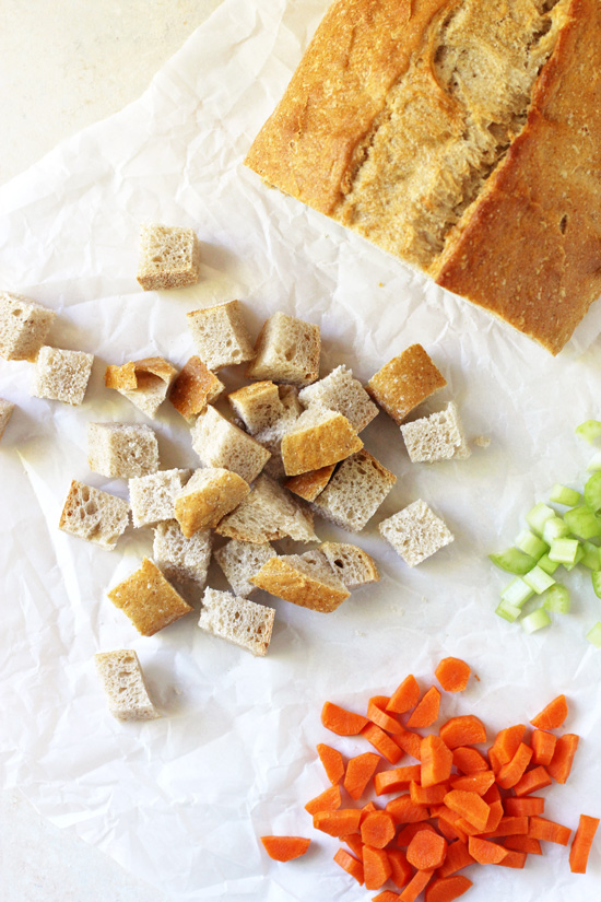 Cubed bread, chopped celery and chopped carrot on parchment paper.
