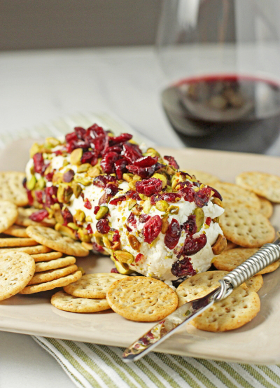 Baked Goat Cheese on a platter with crackers and a cheese knife.