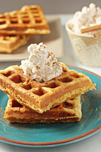 Two Eggnog Waffles on a blue plate topped with cinnamon whipped cream.