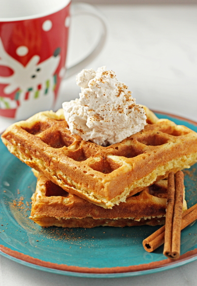 Two holiday Eggnog Waffles on a plate with cinnamon sticks.