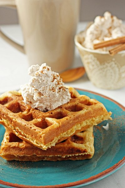 Two Eggnog Waffles on a plate with cinnamon whipped cream.