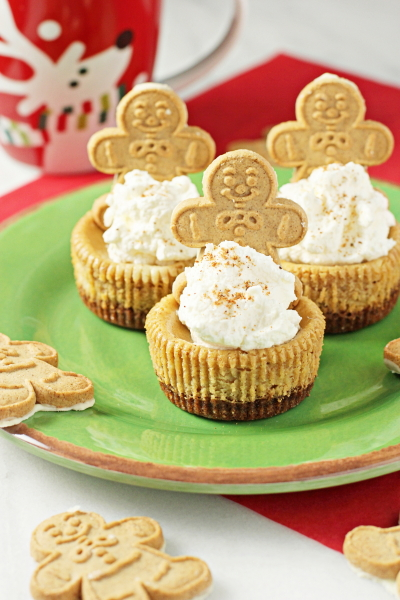 Several Individual Gingerbread Cheesecakes on a plate with gingerbread men cookies.