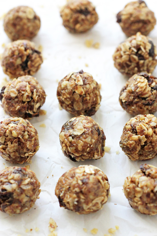 Several Oatmeal Raisin Energy Bites on white parchment paper.