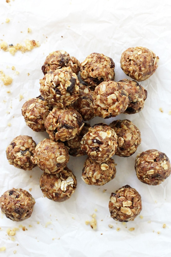 A pile of Oatmeal Raisin Energy Balls on white parchment paper.
