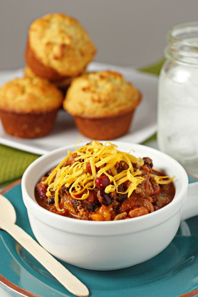 A white bowl filled with Sausage and Beef Chili with cornbread in the background.