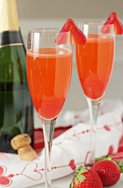 Two Strawberry Bellinis with a bottle of champagne in the background.