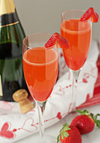 Two Homemade Strawberry Bellinis garnished with sliced strawberries.