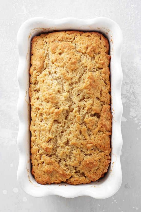 Buttery Honey Beer Bread in a white ruffled loaf pan.