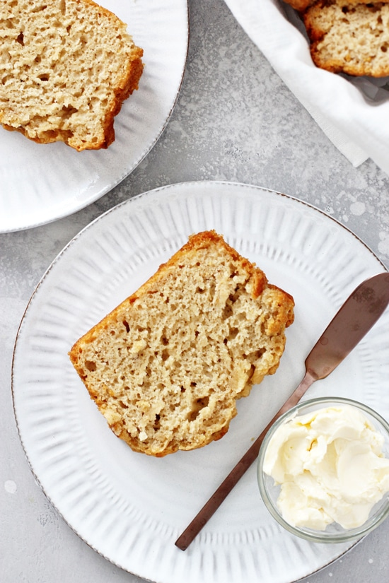 Two slices of Honey Beer Bread on white plates with a knife and butter on the side.