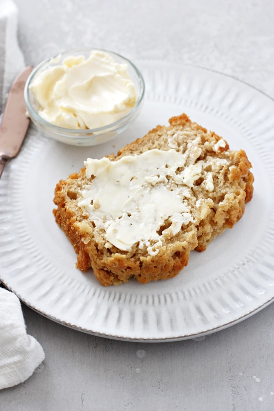 A slice of Buttery Honey Beer Bread on a plate smeared with butter.