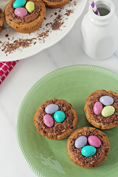 Several Easter Cookie Cups on green and white plates.