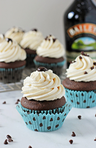 Several Irish Cream Cupcakes on a marble surface.