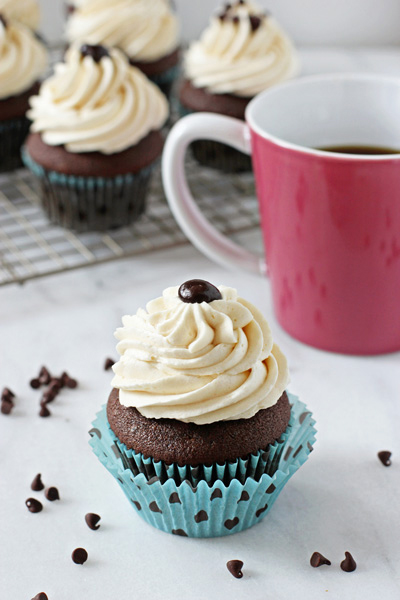 A Baileys Cupcake on a marble surface with a cup of coffee.