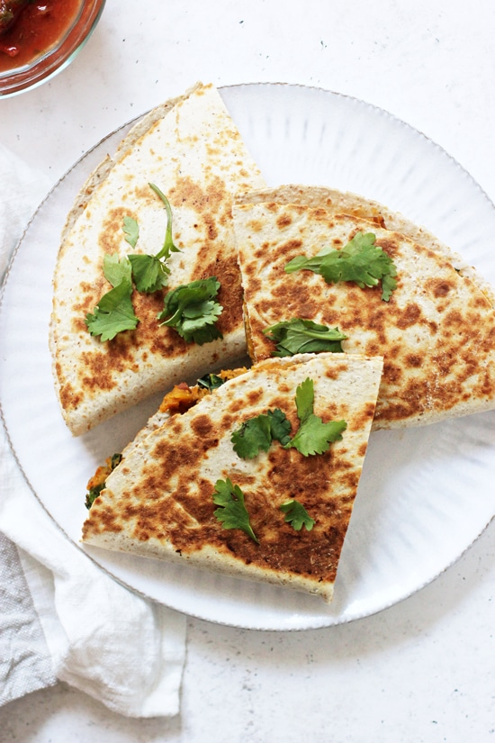 A white plate with three triangles of Sweet Potato Black Bean Quesadillas.