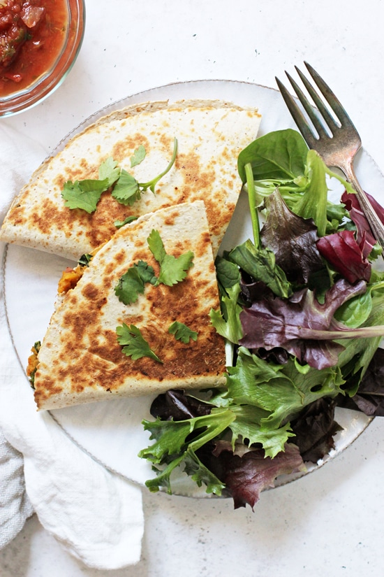 A sliced Sweet Potato and Black Bean Quesadilla on a plate with salad.