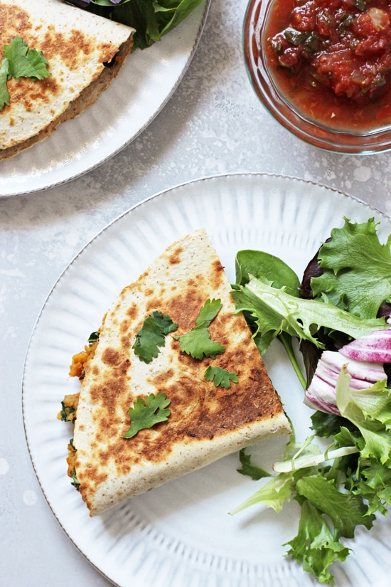 A piece of Sweet Potato Quesadilla on a plate with salad greens.