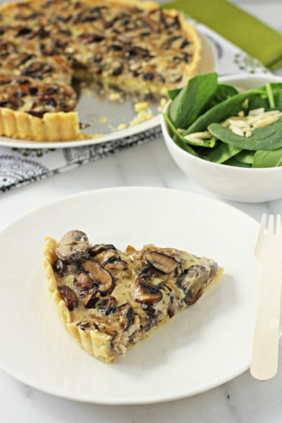 A slice of Wild Mushroom Tart on a white plate with the full tart in the background.