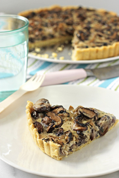 A slice of Wild Mushroom Tart on a plate with a glass of water to the side.