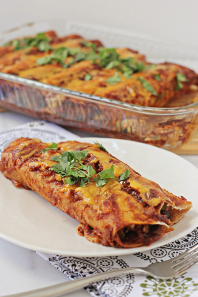 Two Chicken Vegetable Enchiladas on a white plate.